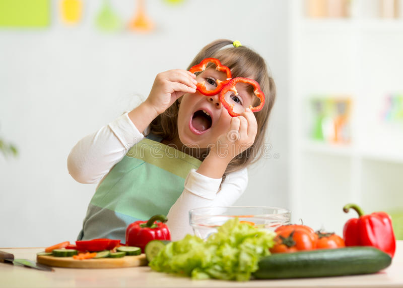 Kid girl having fun with food vegetables stock photos