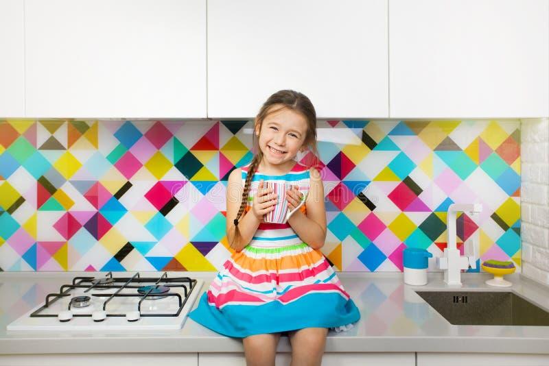 Kid girl having fun at kitchen. Colorful interior royalty free stock photography