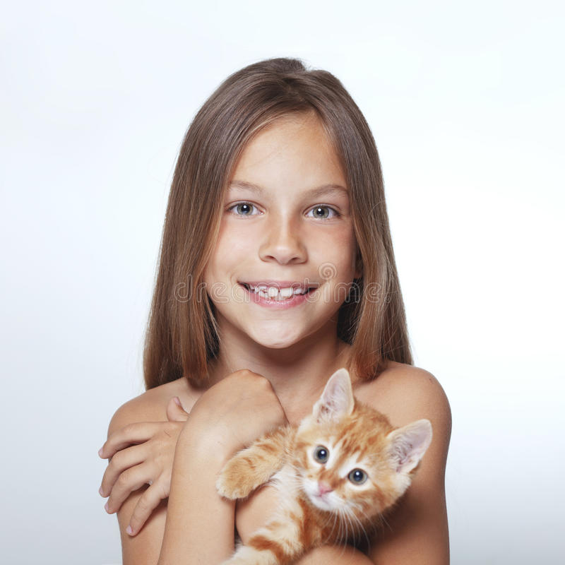 Kid girl with kitten. Portrait of 7 years old kid girl holding small kitten stock image