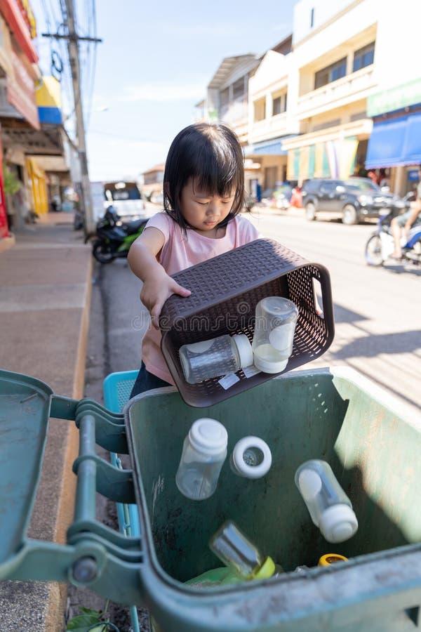 Kid girl leaving milk bottle in to bin. Asian cute kid girl leaving milk bottle in to bin stock photography