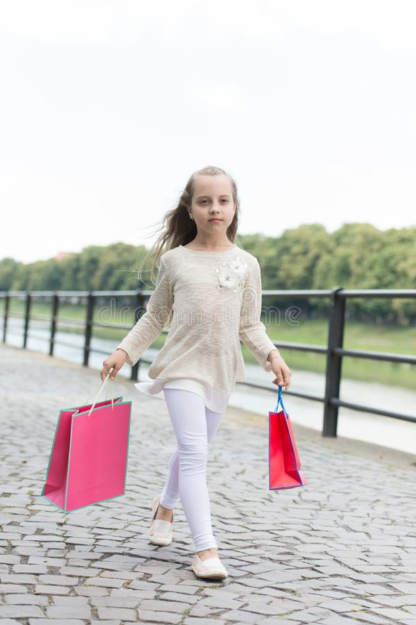Kid girl with long hair fond of shopping. Fashionista girl shopping with pink bags. Girl likes to buy clothes. Shopping. Kid girl with long hair fond of shopping royalty free stock photos