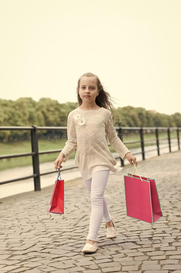 Kid girl with long hair fond of shopping. Fashionista girl shopping with pink bags. Girl likes to buy clothes. Shopping. Kid girl with long hair fond of shopping royalty free stock photo