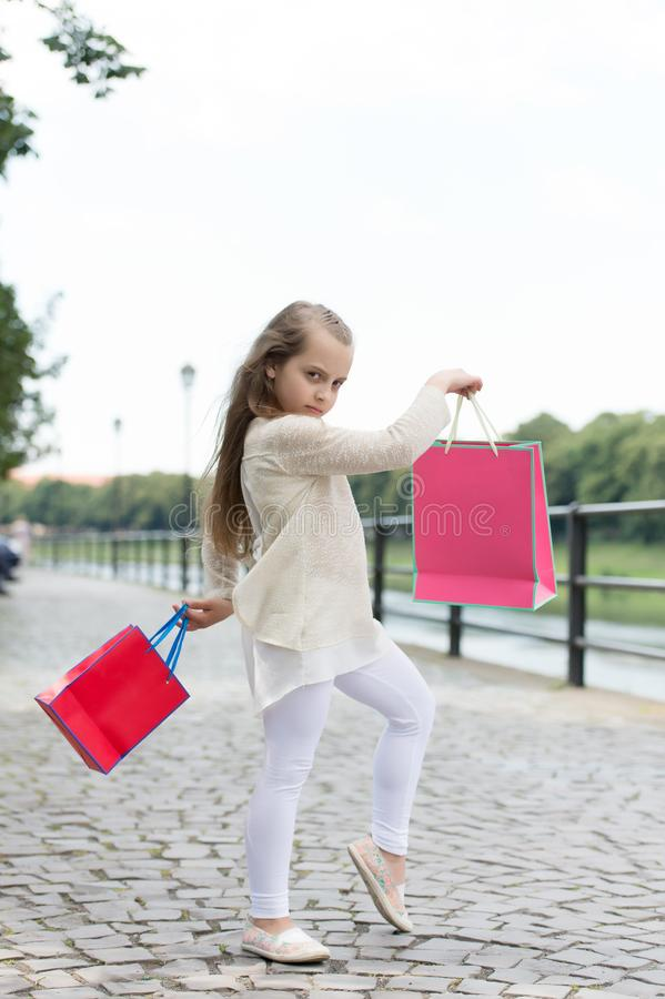 Kid girl with long hair fond of shopping. Fashionista girl shopping with pink bags. Shopping concept. Girl likes to buy. Clothes. Girl calm face carries stock photos