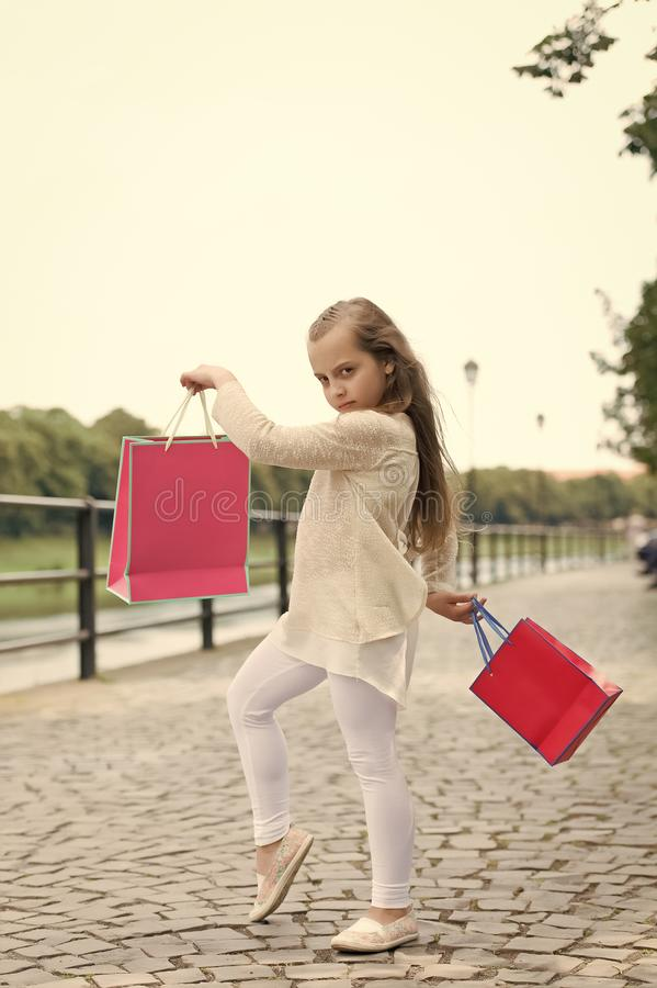 Kid girl with long hair fond of shopping. Fashionista girl shopping with pink bags. Shopping concept. Girl likes to buy. Clothes. Girl calm face carries royalty free stock image