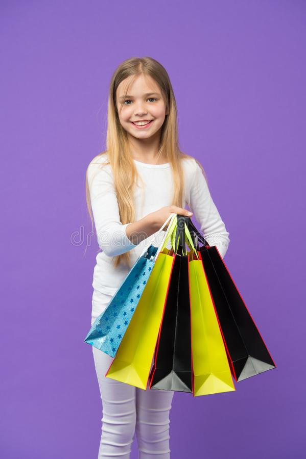 Kid girl with long hair fond of shopping. Girl on smiling face carries bunches of shopping bags, isolated on white. Background. Girl likes to buy fashionable royalty free stock photos