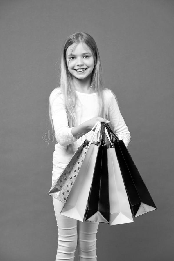 Kid girl with long hair fond of shopping. Girl on smiling face carries bunches of shopping bags, isolated on white. Background. Girl likes to buy fashionable royalty free stock photo