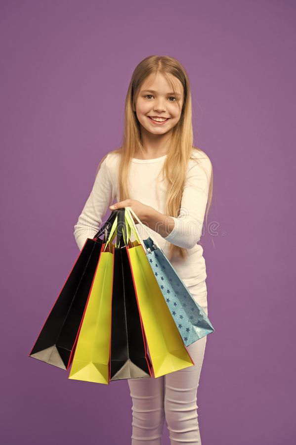 Kid girl with long hair fond of shopping. Girl on smiling face carries bunches of shopping bags, isolated on white. Background. Girl likes to buy fashionable royalty free stock image