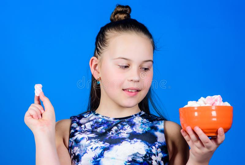 Kid girl with long hair likes sweets and treats. Calorie and diet. Hungry kid. Girl smiling face hold bowl with sweet royalty free stock images