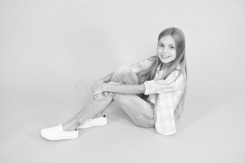 Kid girl with long hair relaxing. Just relaxing here. Feel comfortable and freely. Time to relax. Find place to relax. Girl happy face sit on floor attentive royalty free stock photo