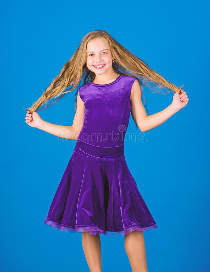 Kid girl with long hair wear dress on blue background. Hairstyle for dancer. How to make tidy hairstyle for kid. Things. You need know about ballroom dance stock photography