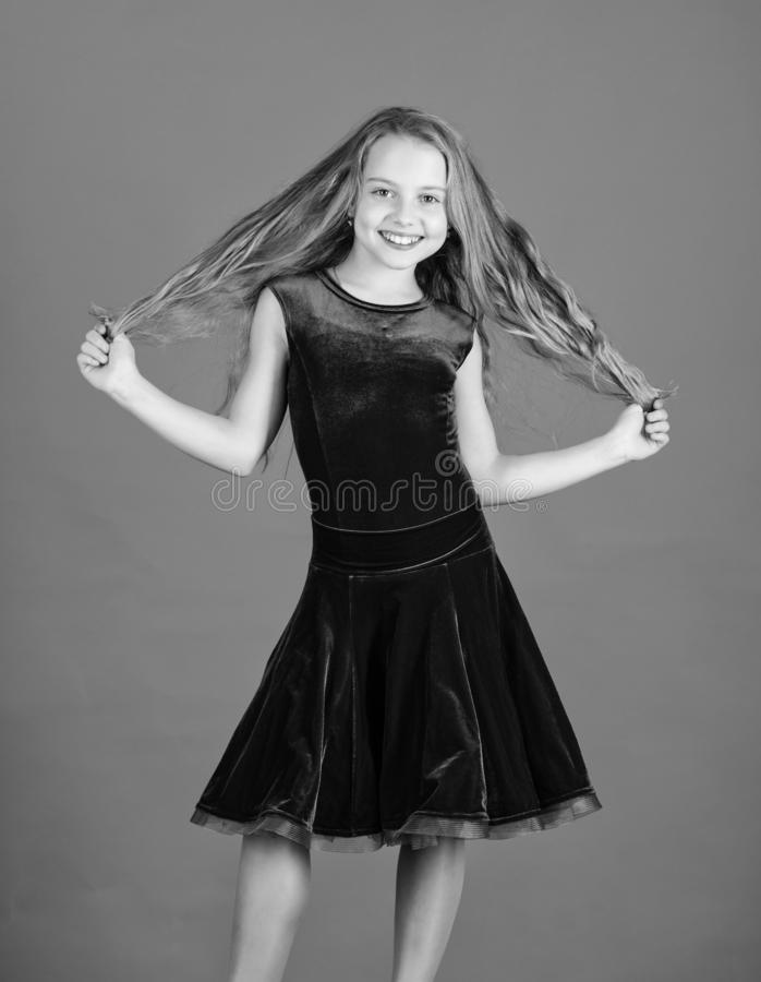 Kid girl with long hair wear dress on blue background. Hairstyle for dancer. How to make tidy hairstyle for kid. Things. You need know about ballroom dance stock photos