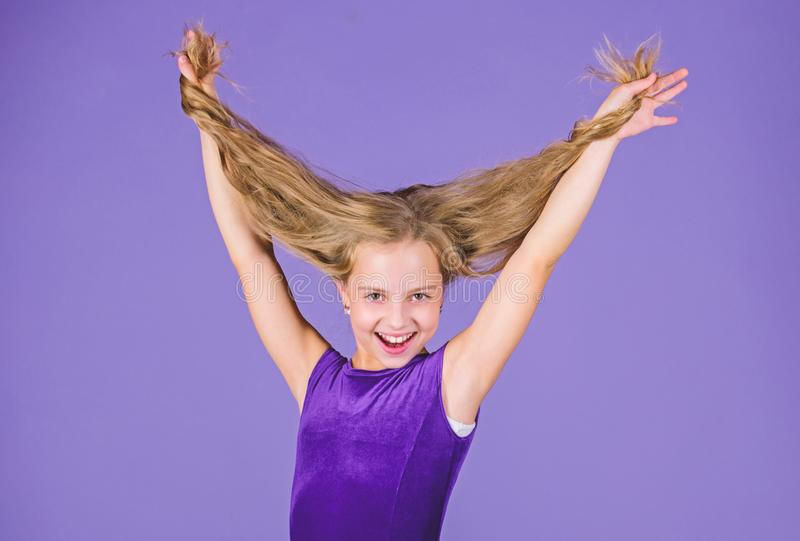 Kid girl with long hair wear dress on violet background. Hairstyle for dancer. How to make tidy hairstyle for kid. Things you need know about ballroom dance royalty free stock images