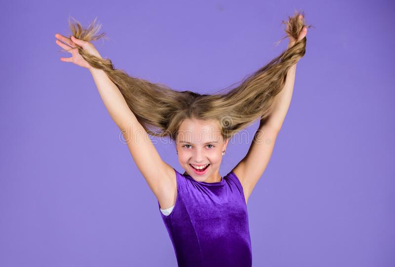 Kid girl with long hair wear dress on violet background. Hairstyle for dancer. How to make tidy hairstyle for kid. Things you need know about ballroom dance royalty free stock photography