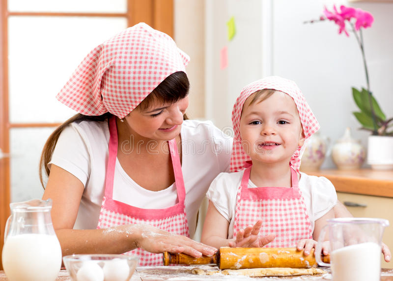kid girl with mother cook and roll out the dough stock image