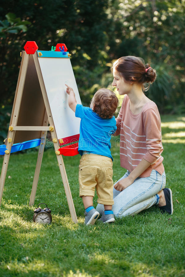 Kid girl with older sister, teacher standing outside in summer autumn park drawing on easel with markers, playing studying. White Caucasian toddler child kid royalty free stock photos