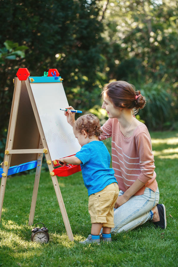 Kid girl with older sister, teacher standing outside in summer autumn park drawing on easel with markers, playing studying. White Caucasian toddler child kid royalty free stock photography