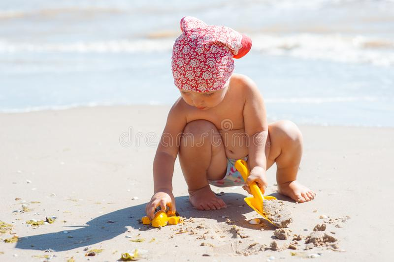 Kid girl play on a beach. Child building sand castle on beach. Summer water fun for family. Girl with toy buckets and spade at the stock photography