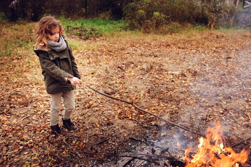 Kid girl playing with fire outdoor in autumn. Forest stock photography