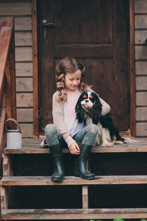 Kid girl playing with her spaniel dog, sitting on stairs at wooden log cabin. In summer stock photos
