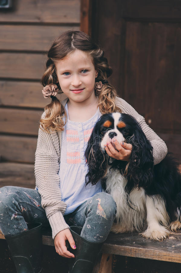 Kid girl playing with her spaniel dog, sitting on stairs at wooden log cabin. In summer stock photo