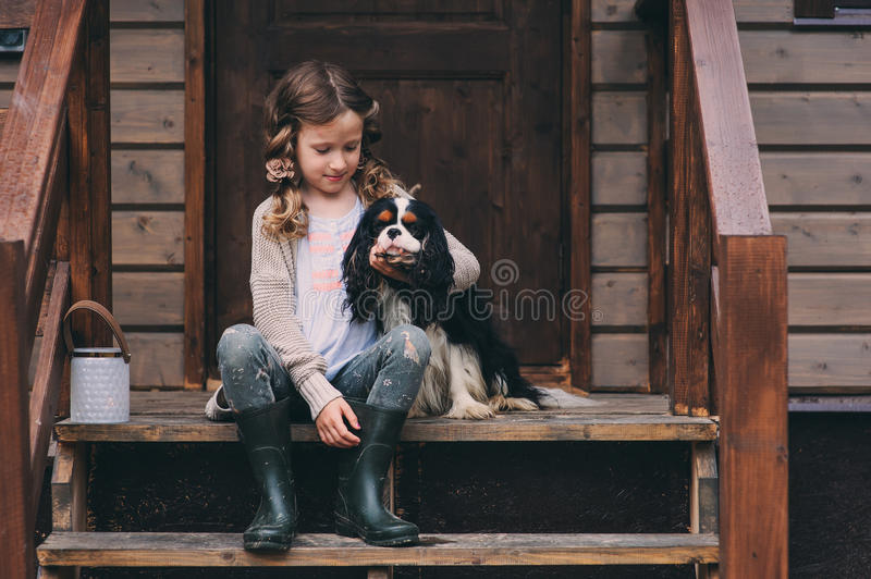 Kid girl playing with her spaniel dog, sitting on stairs at wooden log cabin. In summer royalty free stock image