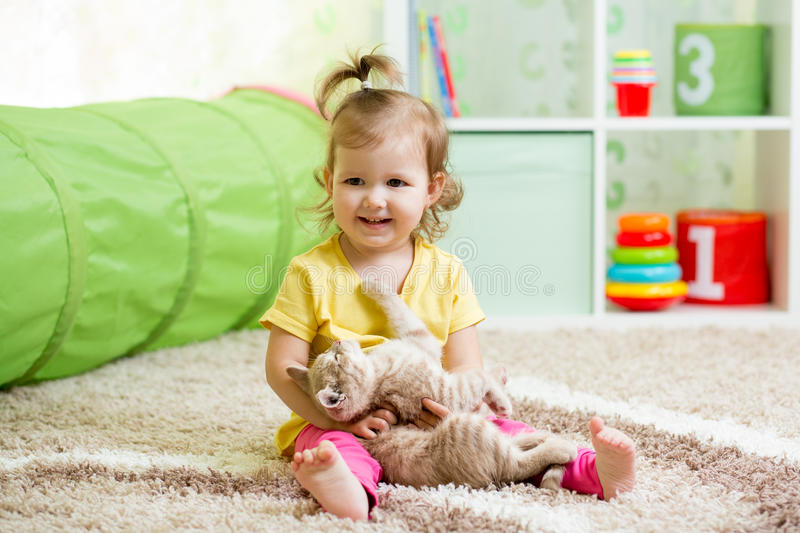 Kid girl playing and hugging loving pet kitten. Little girl playing and hugging loving pet kitten stock photo