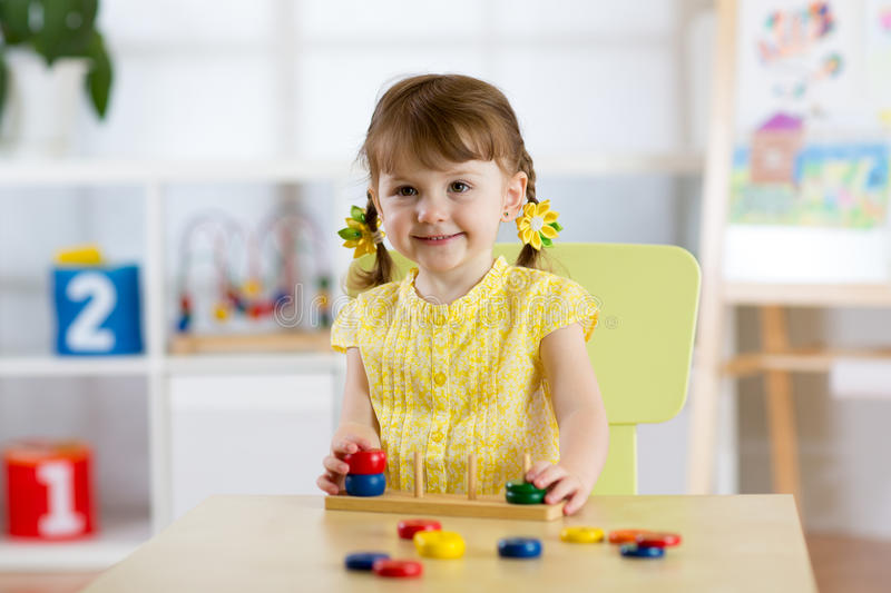 Kid girl playing with logical toy on desk in nursery room or kindergarten. Child arranging and sorting colors and sizes stock image