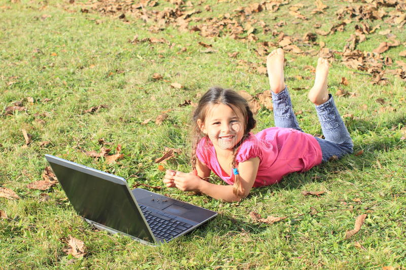 Kid - girl playing with notebook. Smiling barefoot kid - girl lying on the grass and playing with a computer - notebook royalty free stock image