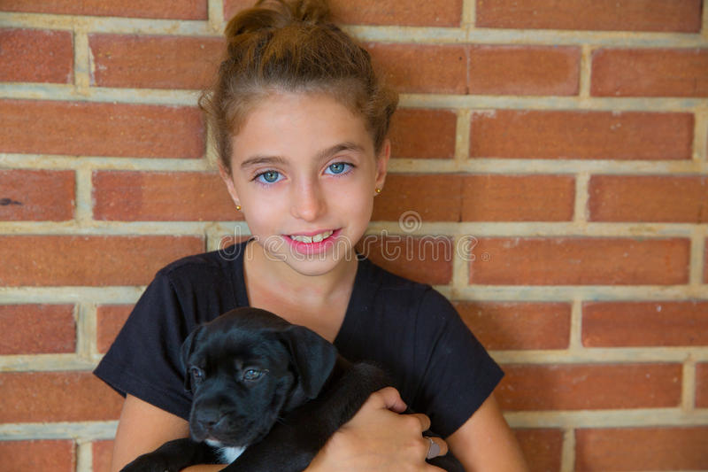 Kid girl playing with puppy dog smiling. With blue eyes royalty free stock photos
