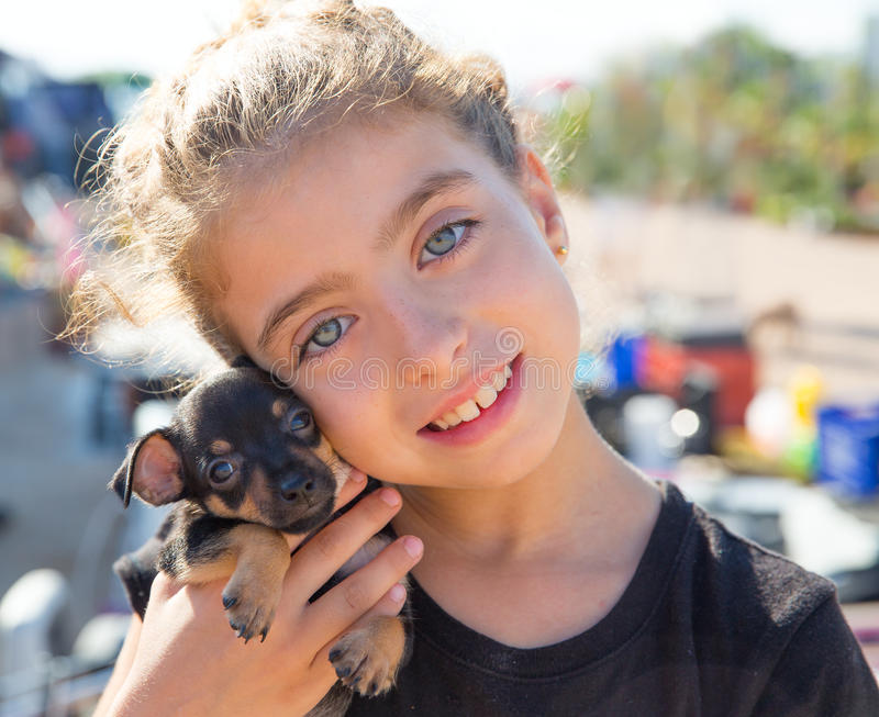 Kid girl playing with puppy dog smiling. With blue eyes stock image