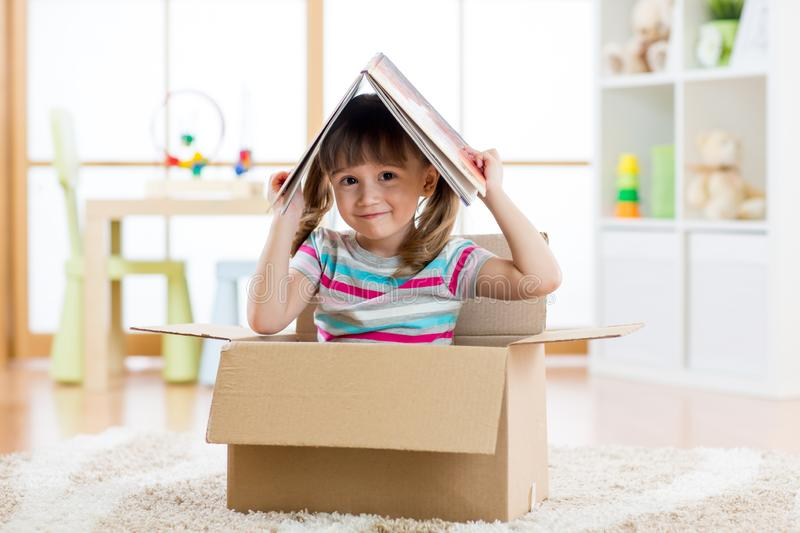 Kid girl playing in a toy house in nursery. Room stock photos