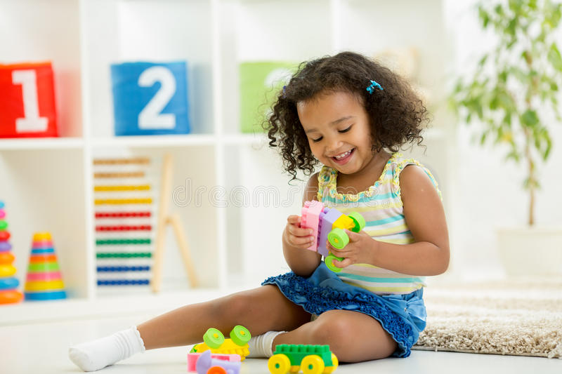 Kid girl playing toys at kindergarten room royalty free stock photography