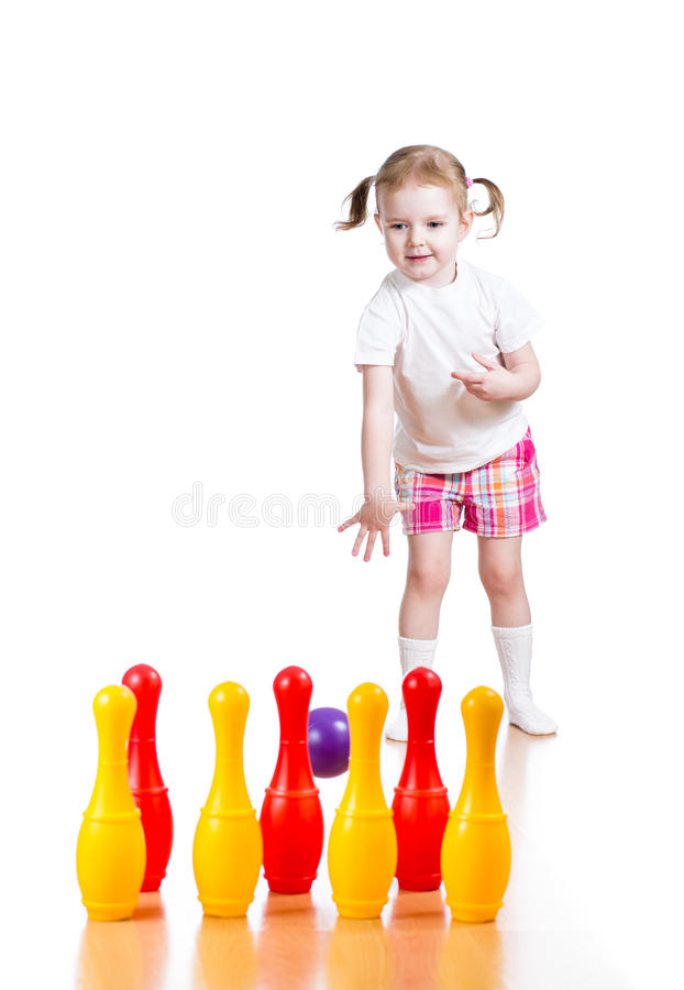 Kid girl plays and throws ball to pins. Kid girl throwing ball to knock down toy bowling pins. Focus on child stock image