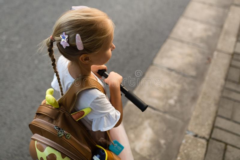 Kid girl pupil from behind walking back to home after learning study school alone with schoolbag, preschool and kindergarten royalty free stock image