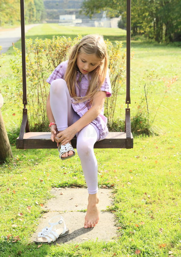 Kid - girl putting on shoes on swing. Little kid - girl putting on her shoes on swing royalty free stock images