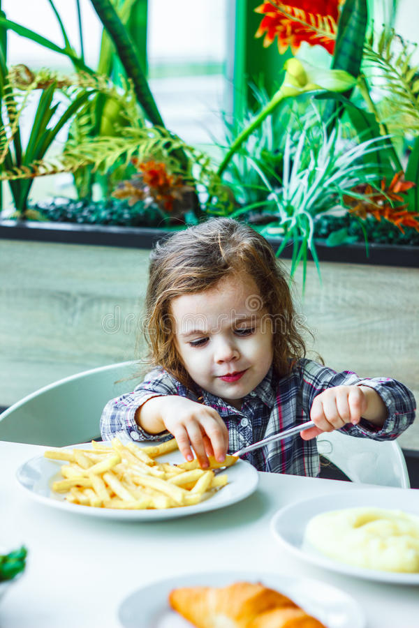 Kid girl in a restaurant eating fast food. Kid girl in a restaurant eating fast food stock photography