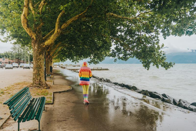 Kid girl riding scooter by the lake on a rainy day. Wearing colorful rain coat and boots. Image taken on lake Geneva, Lausanne, Switzerland royalty free stock photos