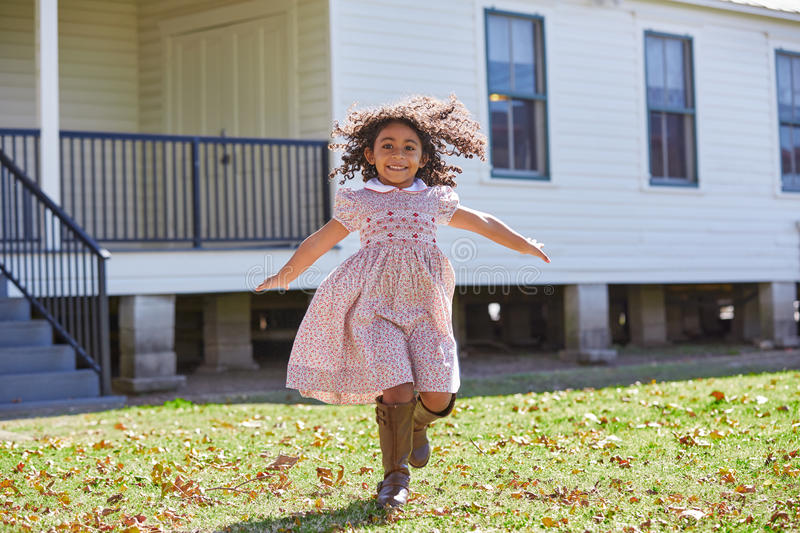 Kid girl running in park with flowers dress royalty free stock images