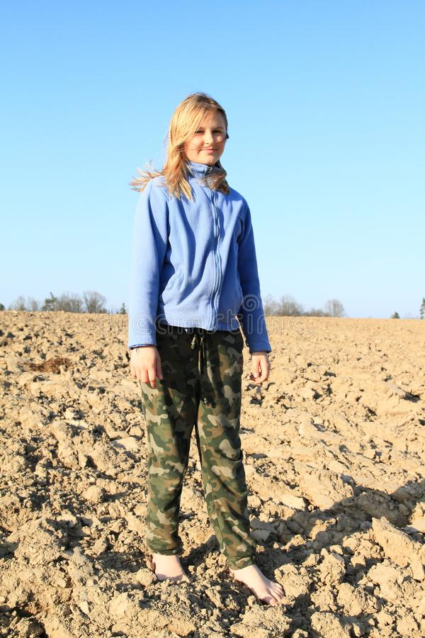 Kid - girl standing on field. Little kid - smiling barefoot girl standing on ground of dried field stock images