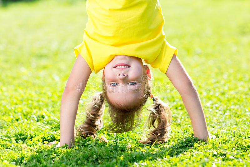 Kid girl standing upside down on her head on grass in summer royalty free stock photography
