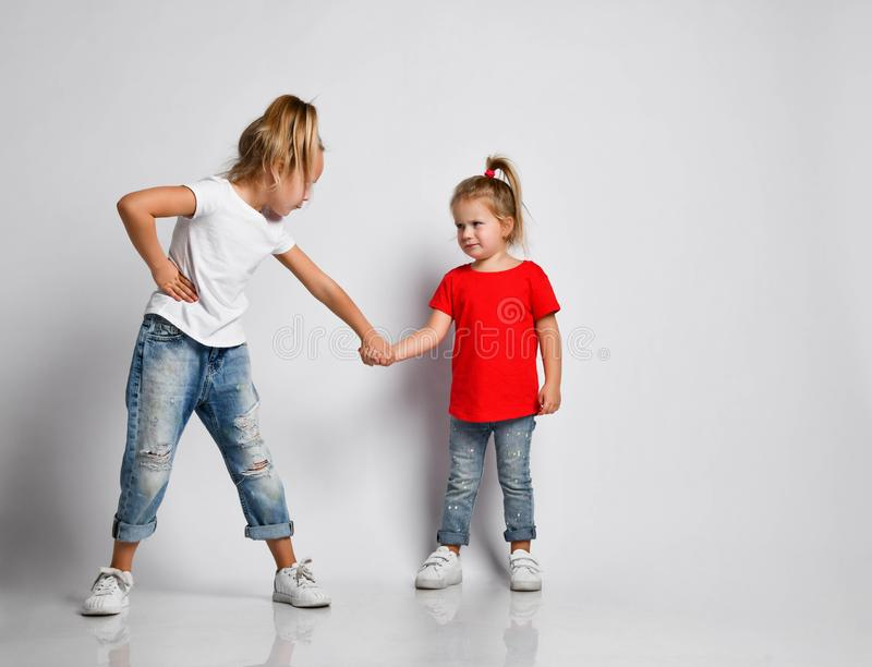 Kid girl is strict to younger sister, holding her hand painfully. Baby girl is trying to endure the pain. Kid girl is strict to younger sister, holding her hand royalty free stock photography