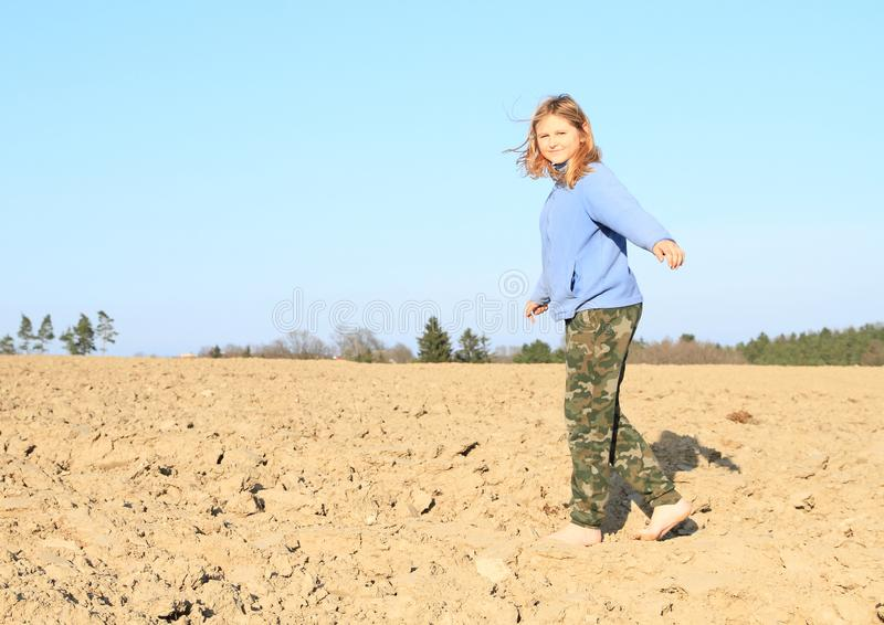 Kid - girl walking on field. Little kid - smiling barefoot girl walking on ground of dried field royalty free stock image