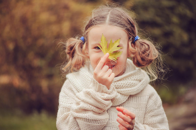 Kid girl walking in the garden in late october or november and playing with maple leaf. Children exploring nature royalty free stock photography
