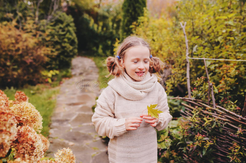 Kid girl walking in the garden in late october or november and playing with maple leaf. Children exploring nature royalty free stock images