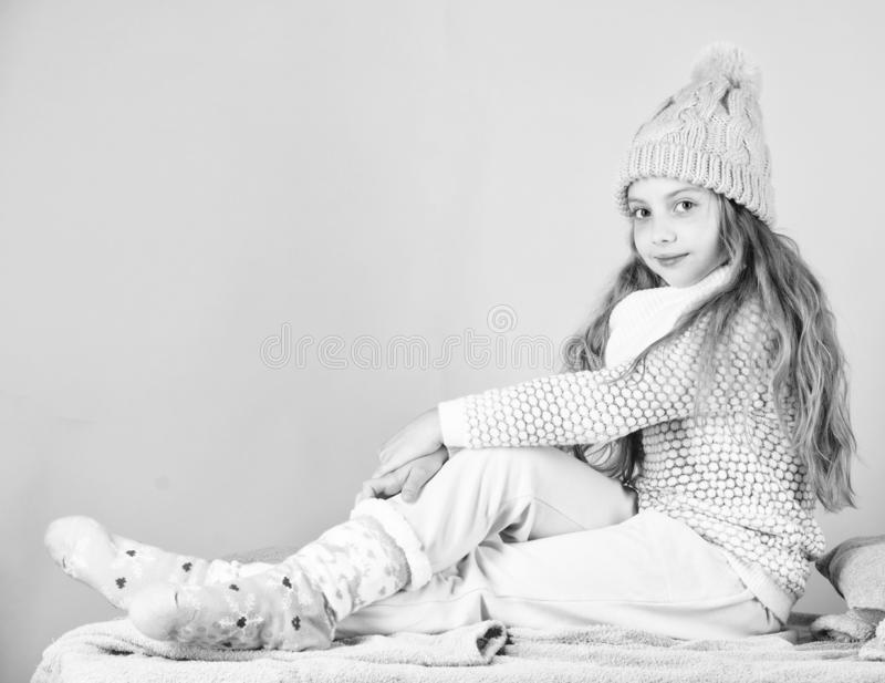 Kid girl wear cute knitted fashionable hat and comfortable cozy clothes. Girl long hair relaxing pink background. Winter. Fashion for children. Kid smiling royalty free stock photography