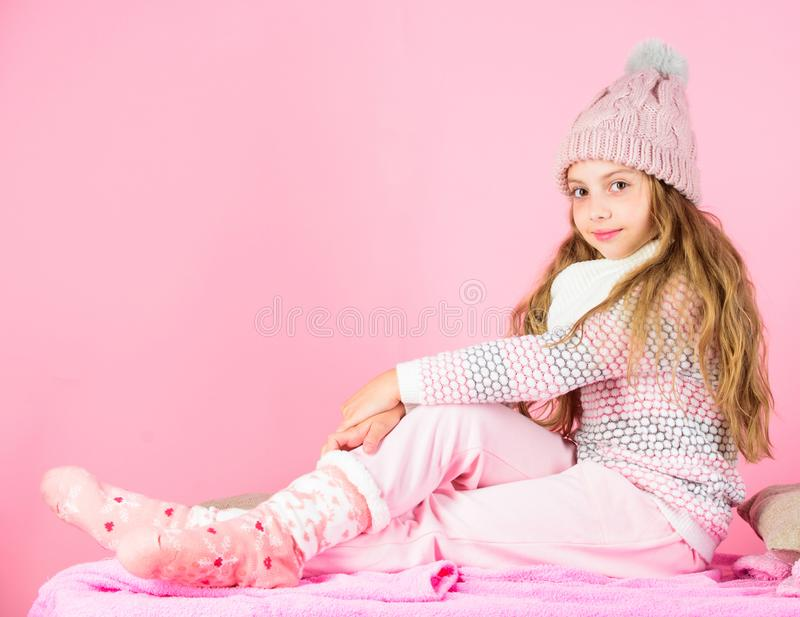 Kid girl wear cute knitted fashionable hat and comfortable cozy clothes. Girl long hair relaxing pink background. Winter. Fashion for children. Kid smiling royalty free stock images