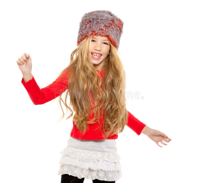 Kid girl winter dancing with red shirt and fur hat. On white background royalty free stock photo