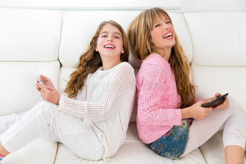 Kid girls having fun playing back to back with tablet pc on sofa stock images
