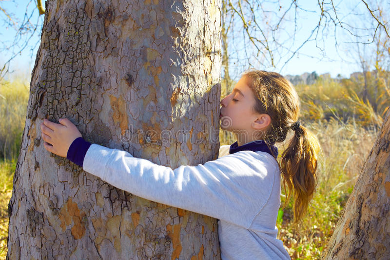 Kid girls loves nature kissing a tree tunk. Kid girls loves nature hug annd kiss a tree tunk in outdoor winter park stock images