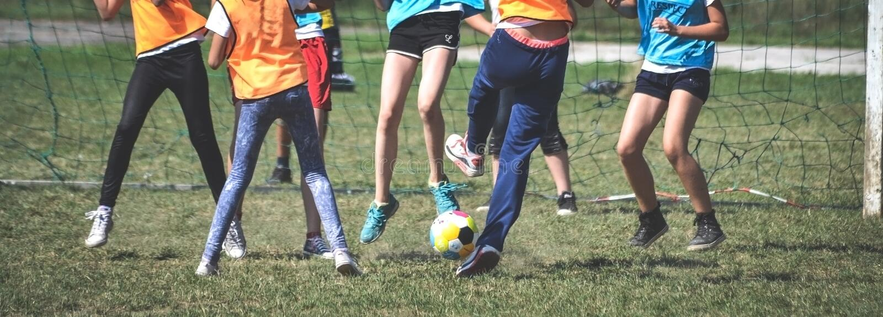Kid girls play football shot on goal. Seven kid girls play football stock image